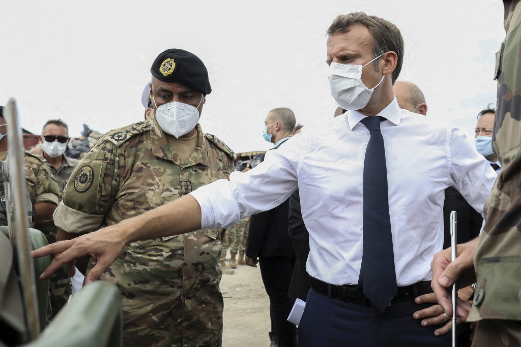 French President Emmanuel Macron gestures toward a board as he meets the military mobilized to help to rebuild the port of Beirut, Tuesday, Sept.1, 20...