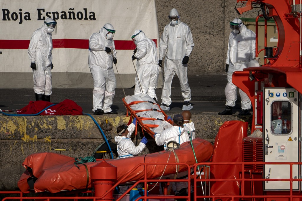 Emergency workers carry a migrant's body after being found dead by the Spanish Maritime Rescue Service, at the Arguineguin port in Gran Canaria island...