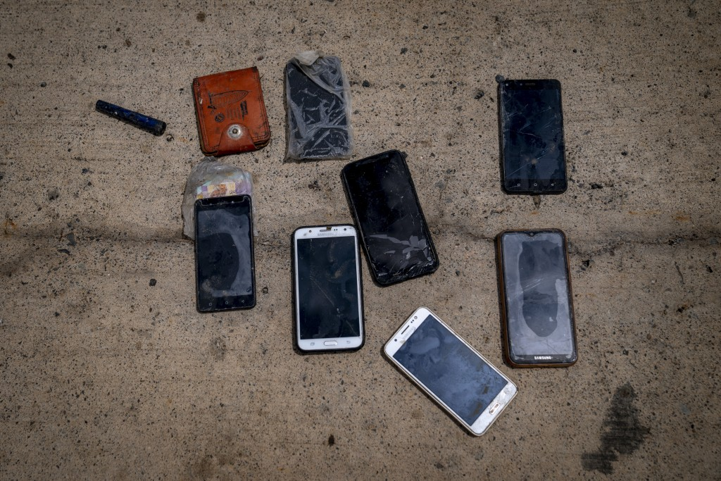 Wet phones and other items are placed on the ground by police officers as they inspect a boat where 15 Malians were found dead adrift in the Atlantic ...