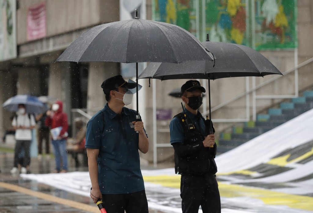 Police officers wear face masks to help protect against the spread of the coronavirus in downtown, South Korea, Wednesday, Sept. 2, 2020. (AP Photo/Le...