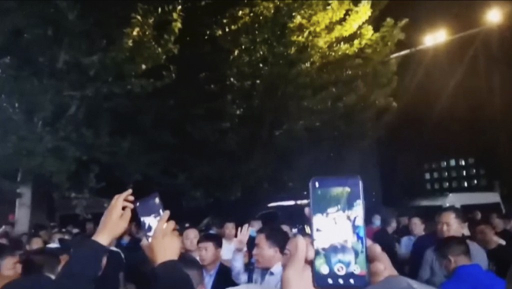 In this image made from video taken in August 2020, parents confront authorities outside a school in Tongliao in Northwestern China's Inner Mongolia r...