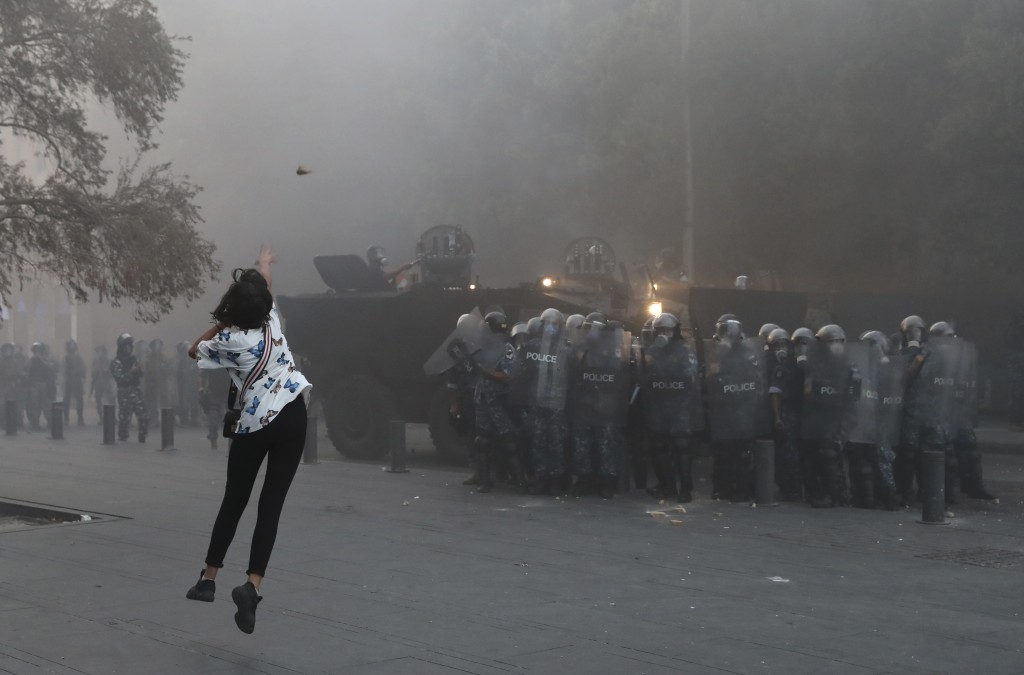 An anti-government protester throws a stone towards riot police during a protest near Parliament Square, In Beirut, Lebanon, Tuesday, Sept. 1, 2020. O...
