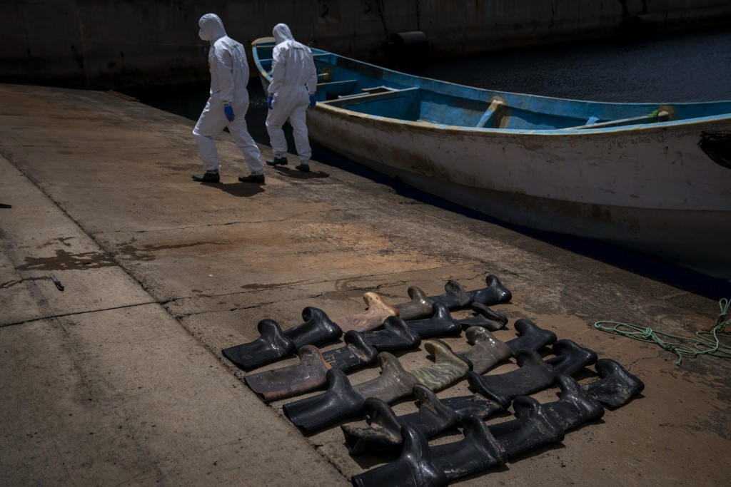 Waterproof boots are placed on the ground by police officers as they inspect a boat where 15 Malians were found dead adrift in the Atlantic on Thursda...