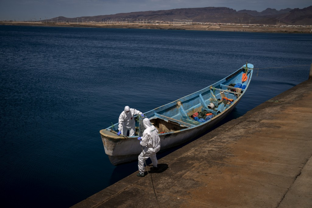 Police officers inspect a boat where 15 Malians were found dead adrift in the Atlantic on Thursday, Aug. 20, 2020 in Gran Canaria island, Spain. The 1...