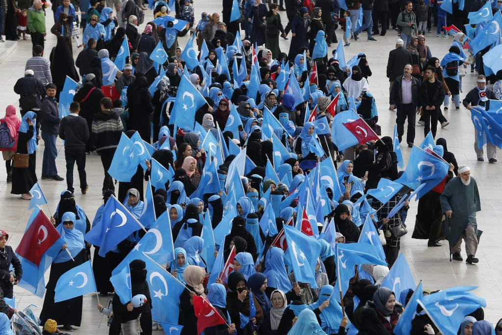 FILE - In this file photo dated Tuesday, Nov. 6, 2018, people from the Uighur community living in Turkey carry flags of what ethnic Uighurs call 'East...