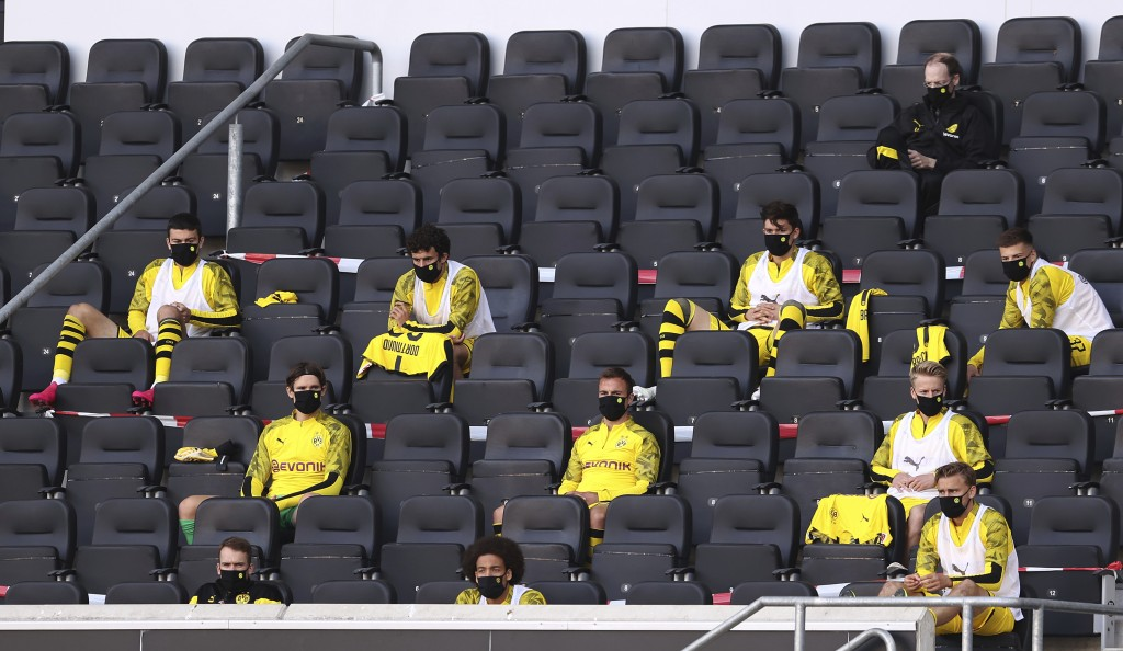 FILE - In this Sunday, May 31, 2020, substitutes for Borussia Dortmund, wearing face masks to protect against coronavirus, look on from the stands dur...