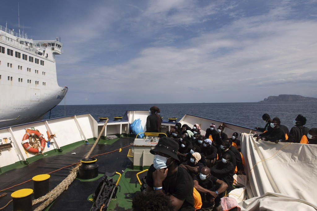 Some of the 353 migrants rescued by Sea-Watch 4 wait to board the quarantine Ferry Gnv Allegra, in front of the port of Palermo, Italy, Wednesday, Sep...