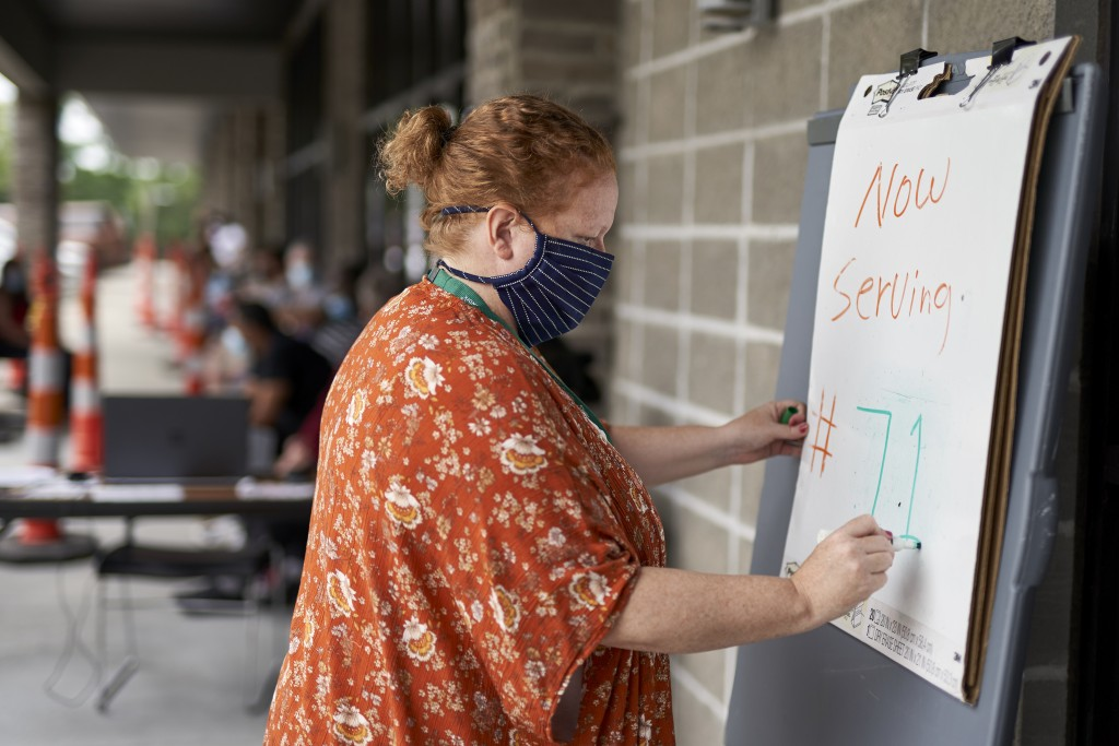 FILE - In this July 15, 2020, file photo, one-stop operator Vickie Gregorio with the Heartland Workforce Solutions updates a whiteboard outside the wo...