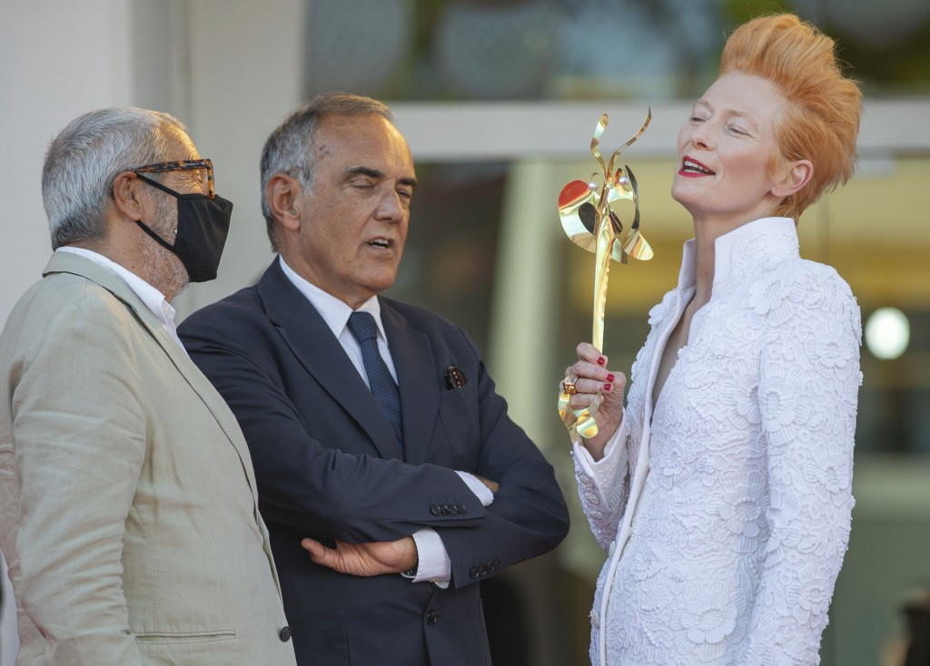 Actress Tilda Swinton, right, talks to festival director Alberto Barbera, center, and the Venice Biennale's president Roberto Cicutto on the red carpe...