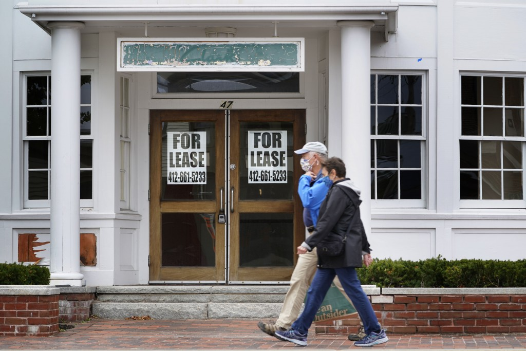 FILE - In this Sept. 2, 2020, file photo, shoppers pass by a former Clark's shoe store that is now one of several vacant retail spaces among the outle...