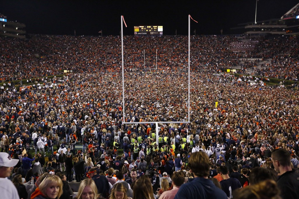FILE - Fans rush the field after Auburn defeated Alabama in the Iron Bowl NCAA college football game, Saturday, Nov. 25, 2017, in Auburn, Ala. What is...