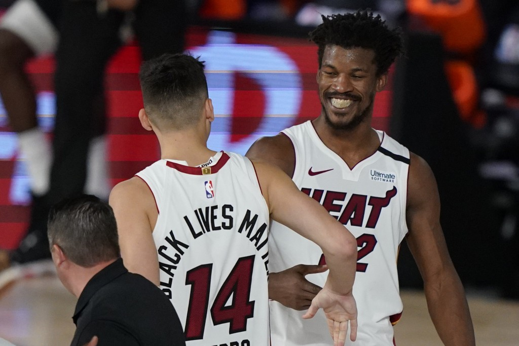 Miami Heat's Tyler Herro (14) and Jimmy Butler (22) react after the Heat beat the Milwaukee Bucks 116-114 in an NBA conference semifinal playoff baske...