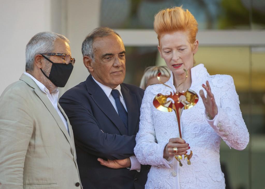 Actress Tilda Swinton, right, talks to festival director Alberto Barbera, center, and the Venice Biennale's president Roberto Cicutto on the red carpe...