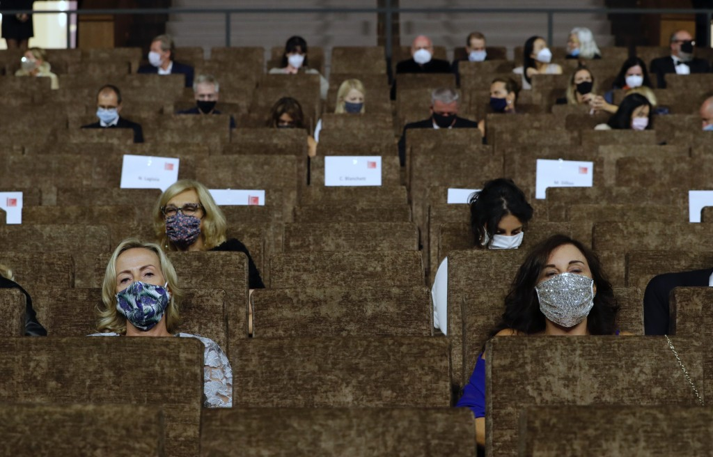 Guests wear face masks as they wait for the start of the opening ceremony of the 77th edition of the Venice Film Festival at the Venice Lido, Italy, W...