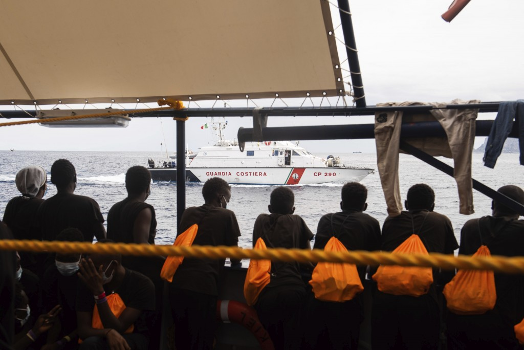 Some of the 353 migrants rescued by Sea-Watch 4 look at an Italian Coast Guard boat as they wait to board the quarantine Ferry Gnv Allegra, in front o...
