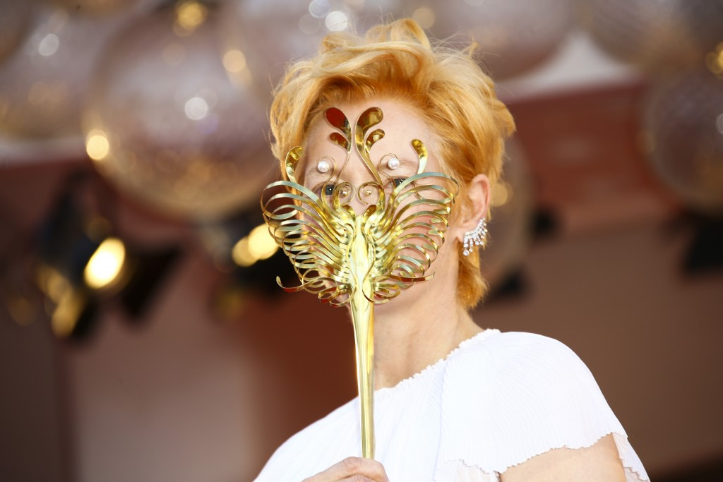 Actress Tilda Swinton holds a carnival mask as she poses for photographers upon arrival at the opening ceremony of the 77th edition of the Venice Film...