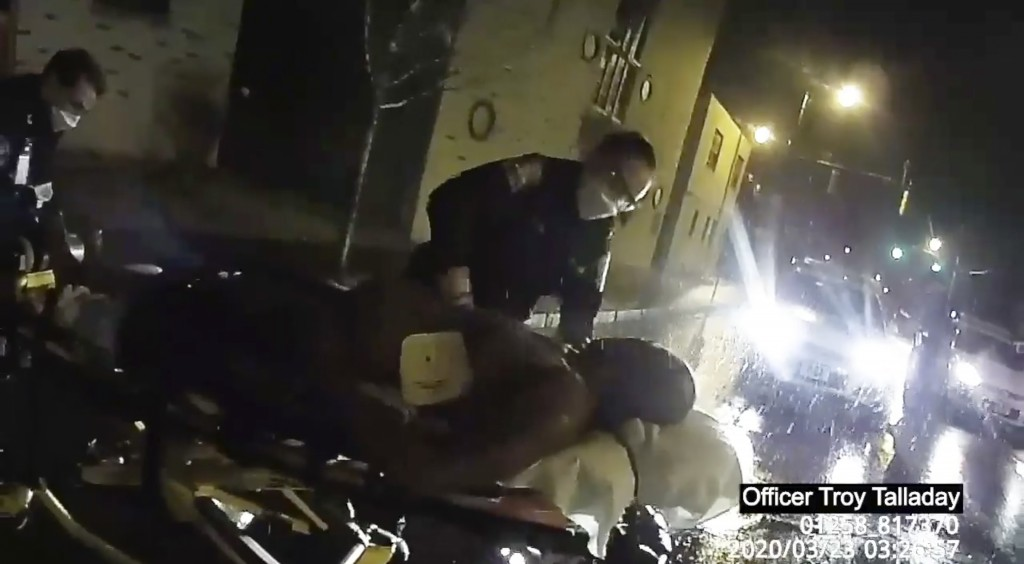 In this image taken from police body camera video provided by Roth and Roth LLP, Rochester police officers prepare to load Daniel Prude into an ambula...