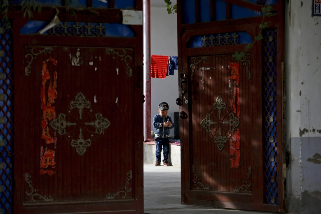 FILE - In this Sept. 20, 2018, file photo, an Uighur child plays alone in the courtyard of a home at the Unity New Village in Hotan, in western China'...