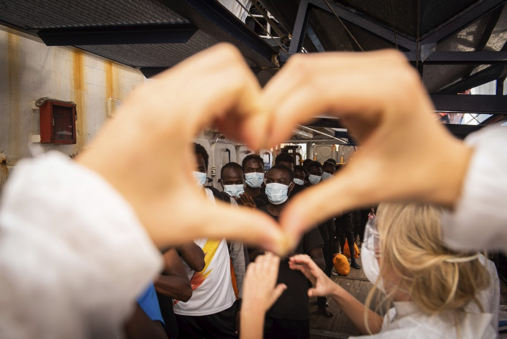 Volunteers salute some of the 353 migrants rescued by Sea-Watch 4 as they prepare to board the quarantine Ferry Gnv Allegra, in front of the port of P...