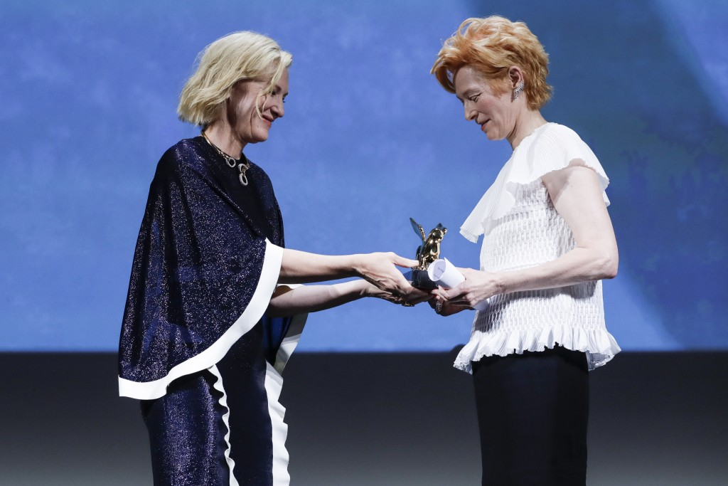 Actress Tilda Swinton, right, holds the Golden Lion for Lifetime Achievement presented by Jury President Cate Blanchett during the opening ceremony of...