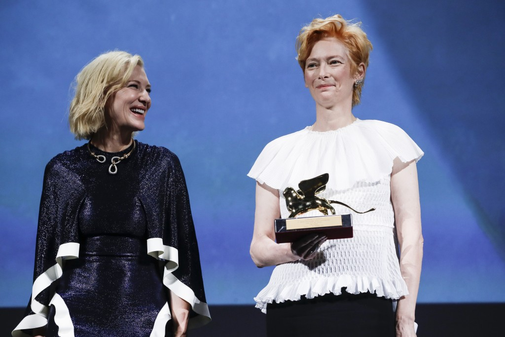 Actress Tilda Swinton, right, holds the Golden Lion for Lifetime Achievement, which was presented by Jury President Cate Blanchett during the opening ...