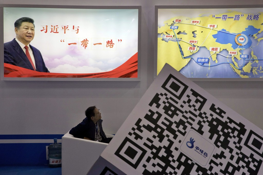 """FILE - In this April 28, 2017, file photo, an attendee at a conference looks up near a portrait of Chinese President Xi Jinping with the words """"Xi Jin..."""