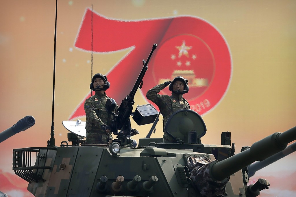 FILE - In this Oct. 1, 2019, file photo, Chinese tank crew members salute during a parade to commemorate the 70th anniversary of the founding of Commu...