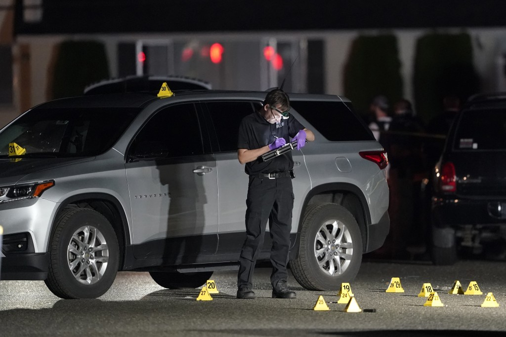 A Washington State Patrol Crime Lab worker looks at evidence markers in the early morning hours of Friday, Sept. 4, 2020, in Lacey, Wash. at the scene...