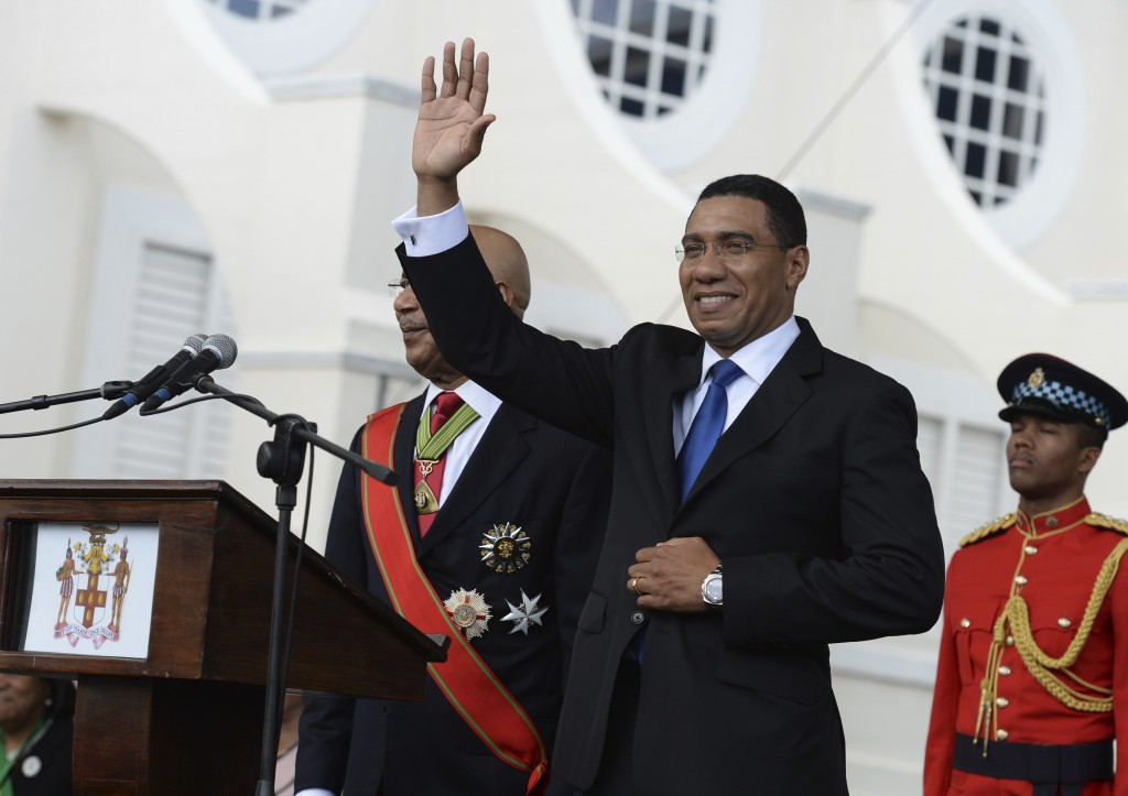 FILE - In this March 3, 2016 file photo, Jamaican Prime Minister Andrew Holness waves to the crowd after being sworn into office, in Kingston, Jamaica...