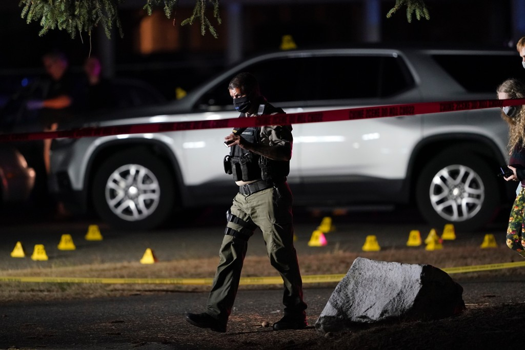 Police walk past evidence markers at the scene where a man suspected of fatally shooting a supporter of a right-wing group in Portland, Ore., last wee...