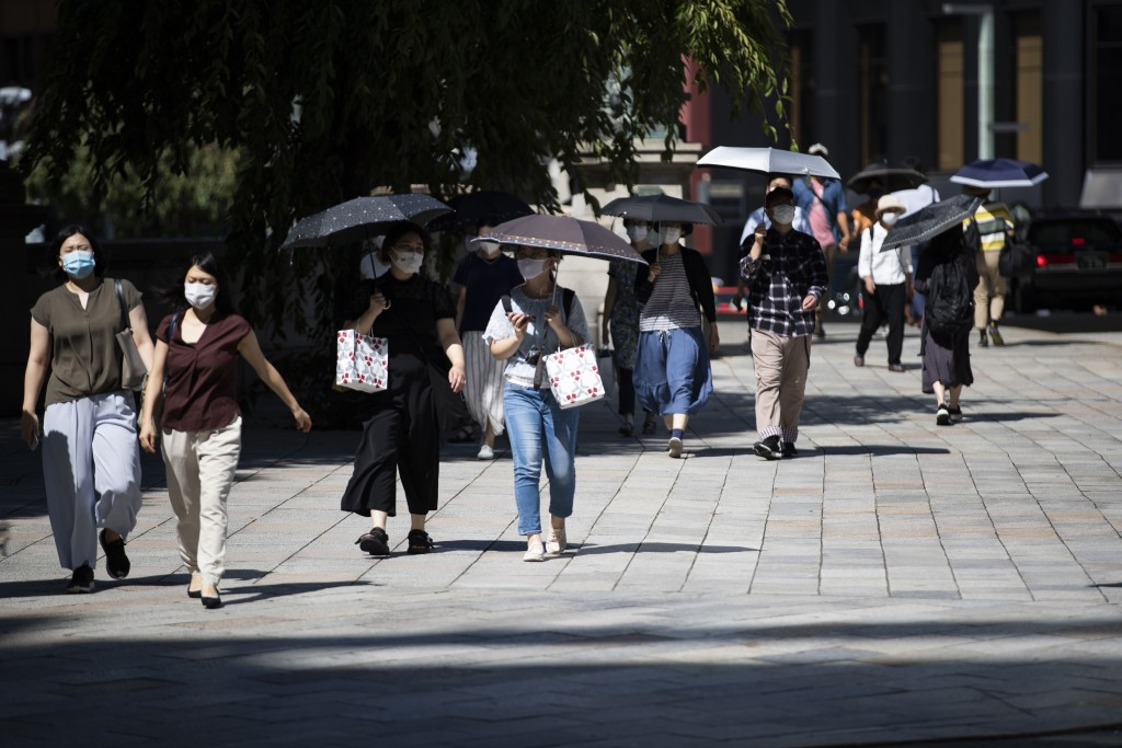 People wearing face masks to help curb the spread of the coronavirus move along a pedestrian walkway in Tokyo on Friday, Sept. 4, 2020. (AP Photo/Hiro...