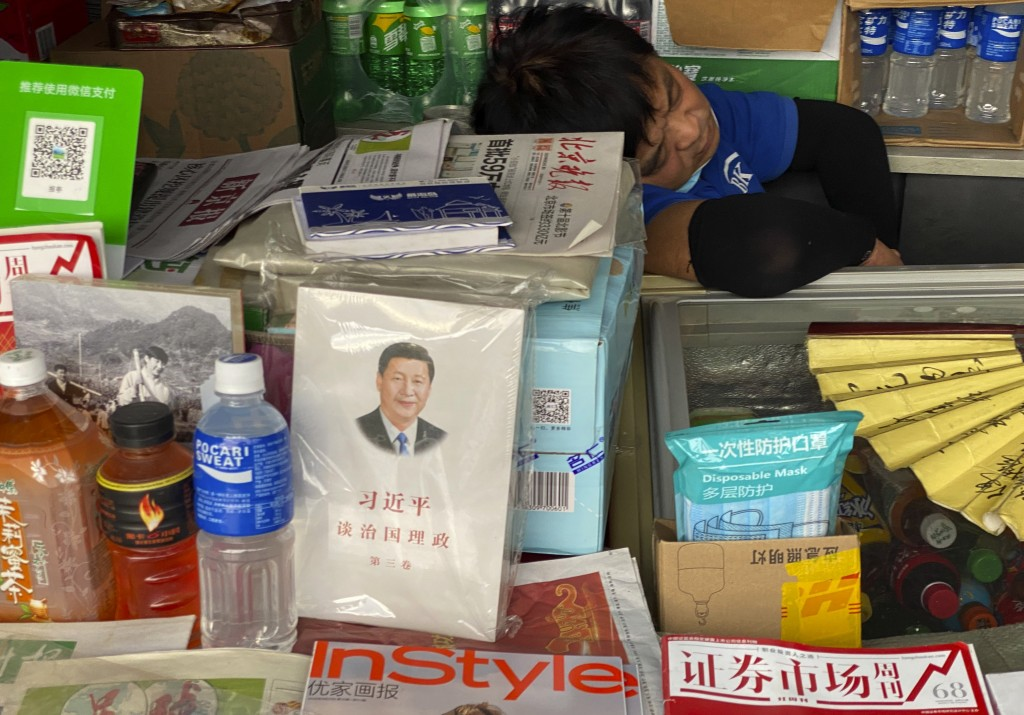 """A newspaper vendor naps near a copy of the book entitled """"Xi Jinping on Governance"""" on sale in Beijing on Monday, Aug. 31, 2020. Seventy-five years af..."""