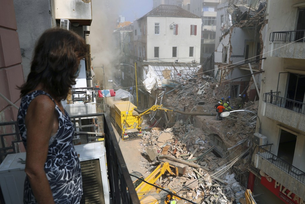 A woman stands on her balcony as she looks at rescuers searching at the site of a collapsed building in Beirut, Lebanon, Friday, Sept. 4, 2020. A puls...