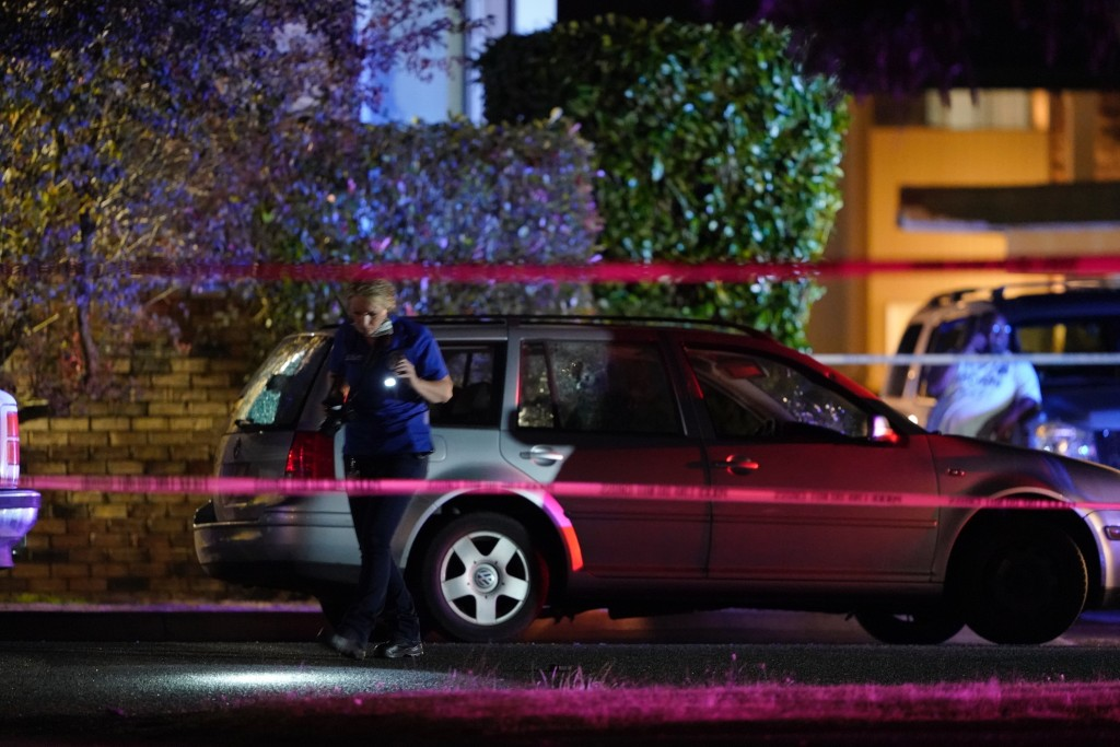 An investigator works at a scene where a man suspected of fatally shooting a supporter of a right-wing group in Portland, Ore., last week was killed a...
