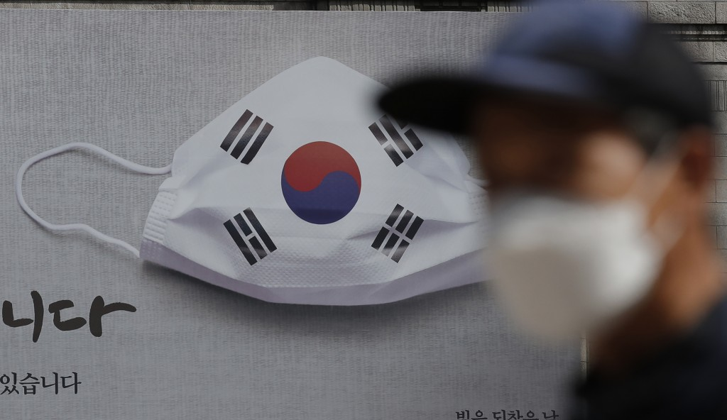 A man wearing a face mask walks near a banner displaying as a part of campaign to overcome the coronavirus in Seoul, South Korea, Friday, Sept. 4, 202...
