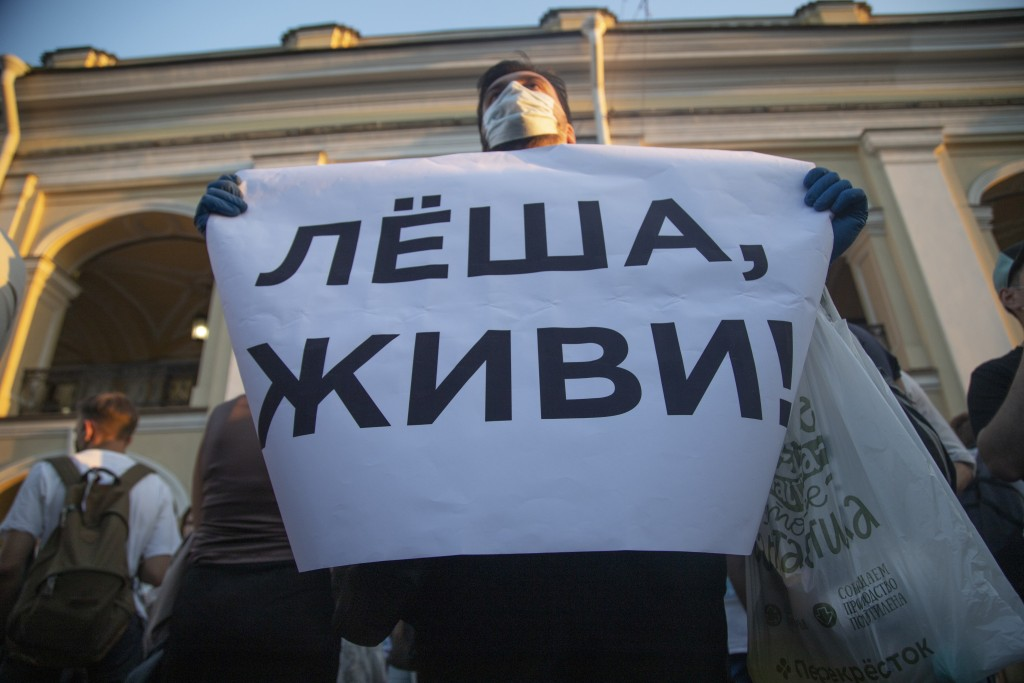 """FILE - In this Aug. 20, 2020, file photo, a protester holds a poster reading """"Lyosha, you must live!"""" in support of Russian opposition leader and corr..."""