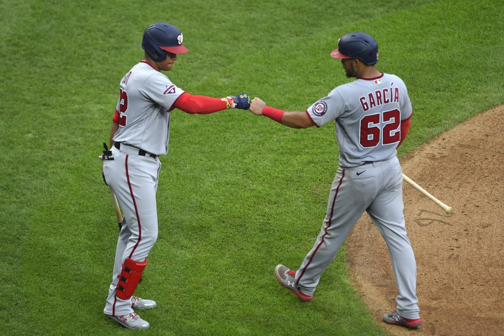 Washington Nationals' Juan Soto, left, fist-bumps Luis Garcia (62) after Garcia scored on a sacrifice by Trea Turner during the fifth inning of the te...