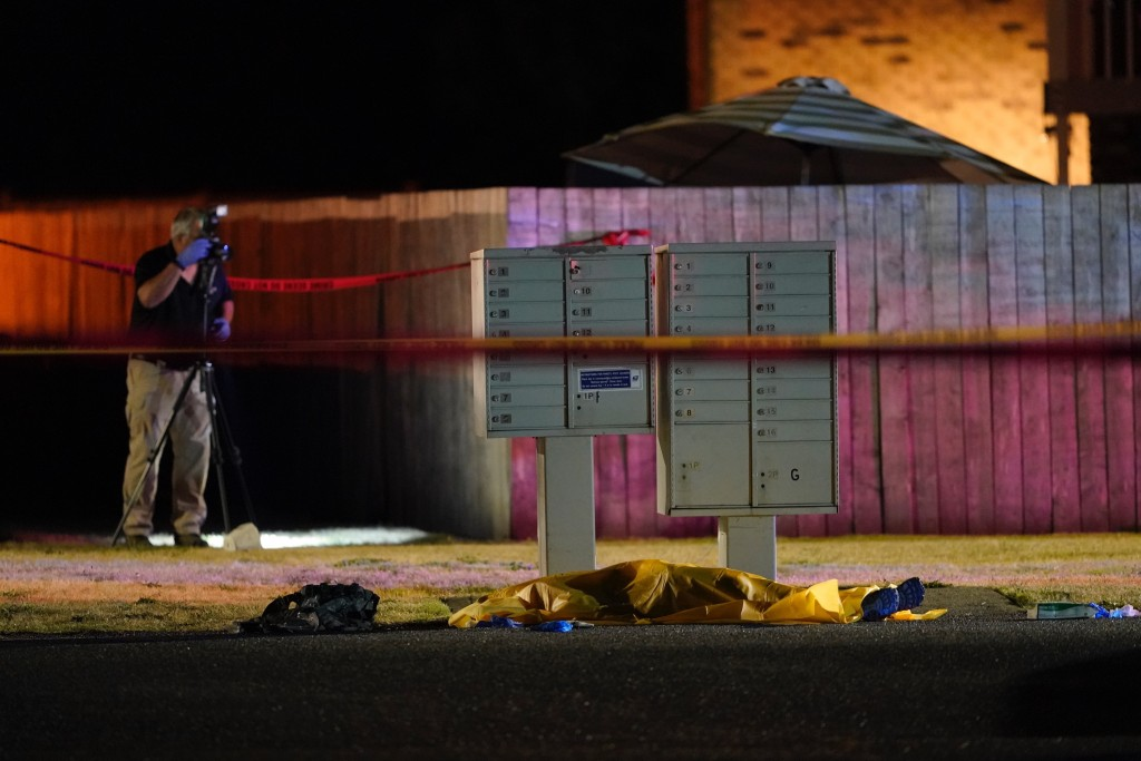 Officials work at a scene late Thursday, Sept. 3, 2020, where a man suspected of fatally shooting a supporter of a right-wing group in Portland, Ore.,...