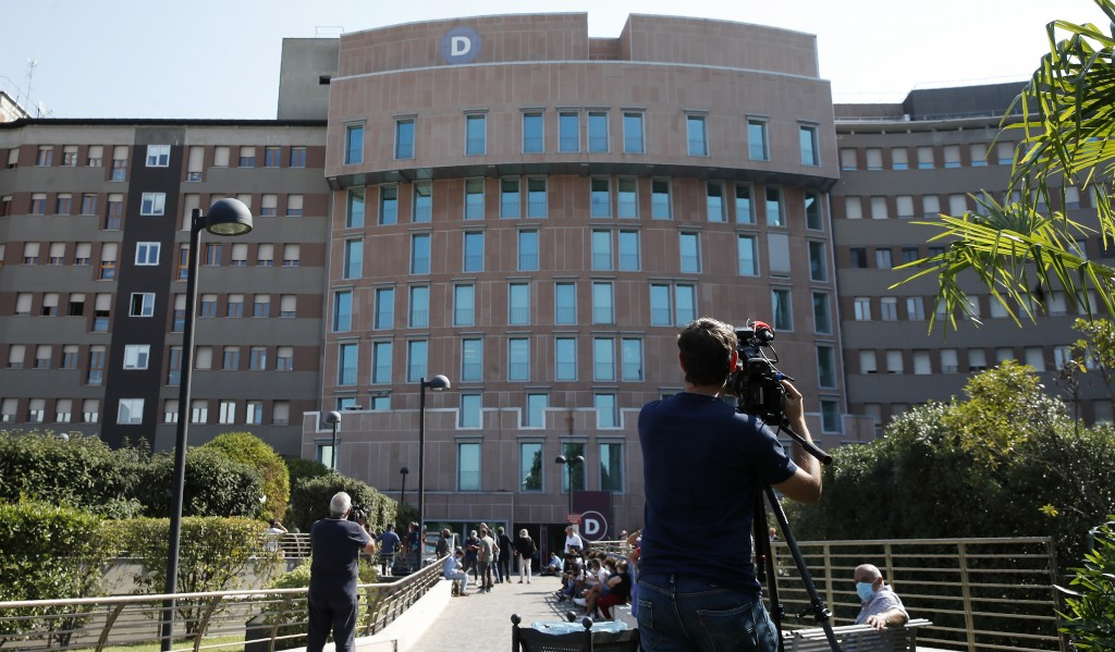 A cameraman films an exterior of the San Raffaele hospital where former Italian premier Silvio Berlusconi is hospitalized, in Milan, Italy, Friday, Se...