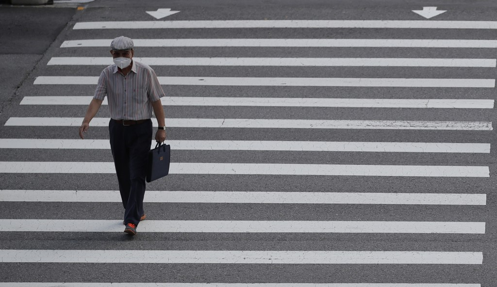 A man wearing a face mask to help curb the spread of the coronavirus walks across a pedestrian crosswalk in downtown Seoul, South Korea, Friday, Sept....
