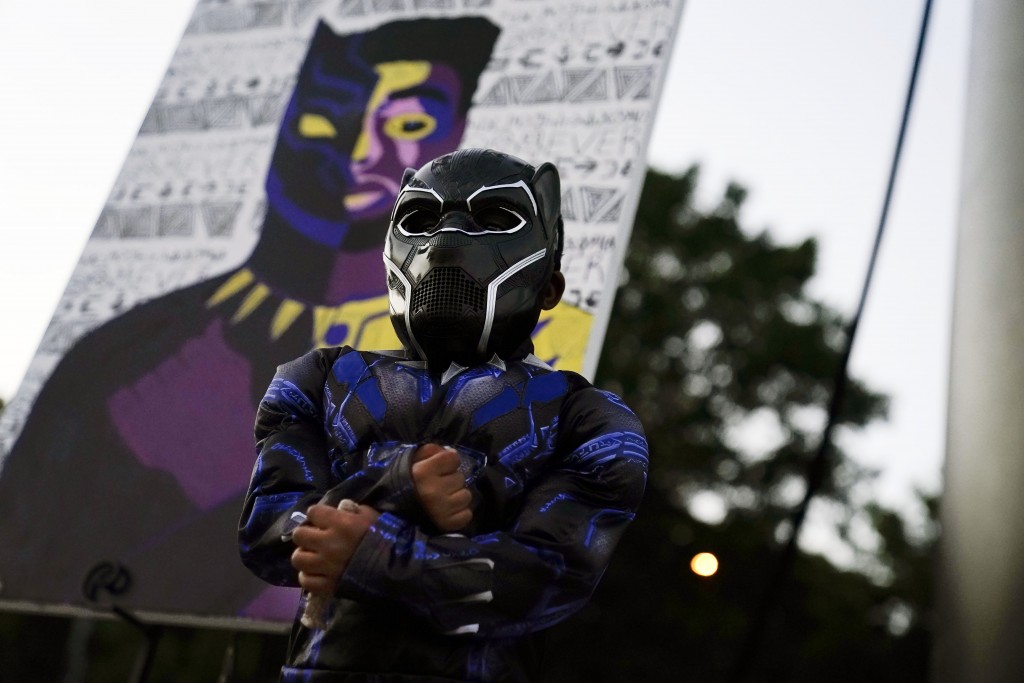 Mason Wilkes, 4, of South Carolina, poses for his father in a Black Panther costume, in front of a painting during a Chadwick Boseman Tribute on Thurs...