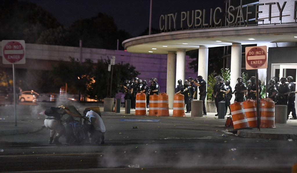 Demonstrators cover from chemical irritants released by police in front of the Public Safety Building in Rochester, N.Y., Thursday, Sept. 3, 2020. Sev...