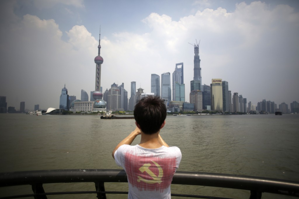 In this Aug. 7, 2013, file photo, a visitor wearing a T-shirt printed with the insignia of the Chinese Communist Party looks at the skyscrapers at the...