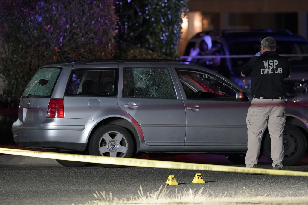 A Washington State Patrol official takes photos near evidence markers and a car with broken windows, Thursday, Sept. 3, 2020, in Lacey, Wash. at the s...