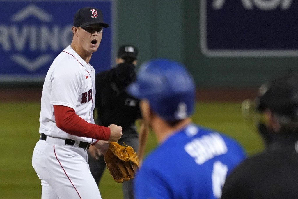 Boston Red Sox relief pitcher Austin Brice, left, pumps his fist after striking out Toronto Blue Jays' Travis Shaw with the bases loaded to end the to...