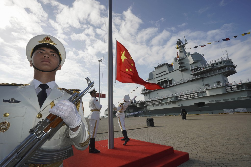 FILE - In this Dec. 17, 2019, file photo and released by Xinhua News Agency, Chinese honor guard raise the Chinese flag during the commissioning cerem...