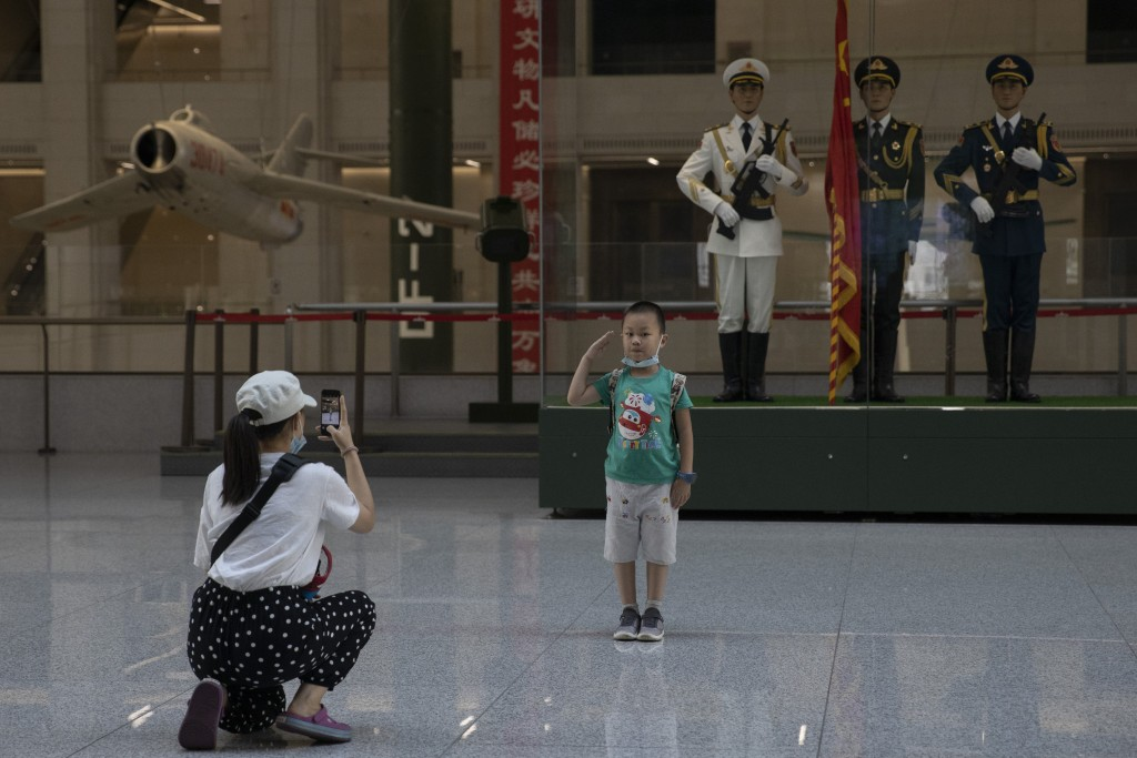 A child salutes for a photo near statues of Chinese military honor guards at the military museum in Beijing on Thursday, Sept. 3, 2020. Seventy-five y...