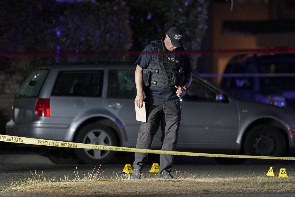 A Washington State Patrol official walks near evidence markers and a car with broken windows, Thursday, Sept. 3, 2020, in Lacey, Wash. at the scene wh...