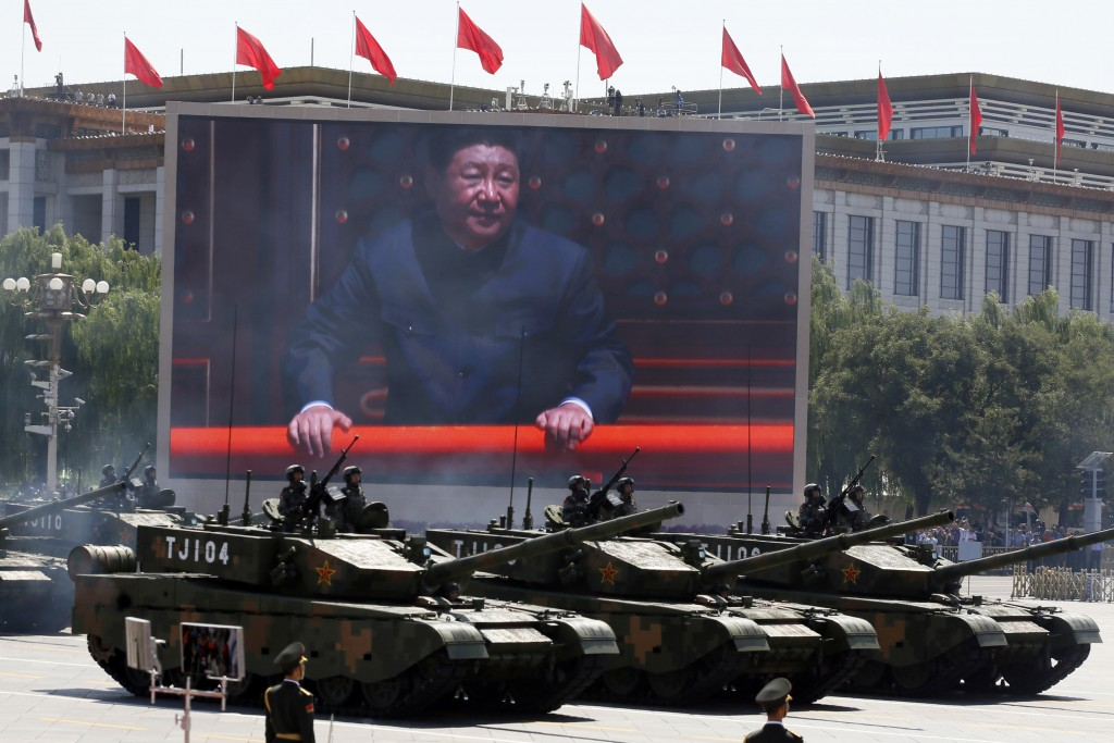 FILE - In this Thursday, Sept. 3, 2015 file photo, Chinese President Xi Jinping is displayed on a screen as Type 99A2 Chinese battle tanks take part i...