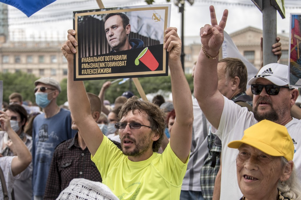 """FILE - In this Aug. 22, 2020, file photo, a man holds a poster with a portrait of Kremlin critic Alexei Navalny reading """"Navalny was poisoned, we know..."""